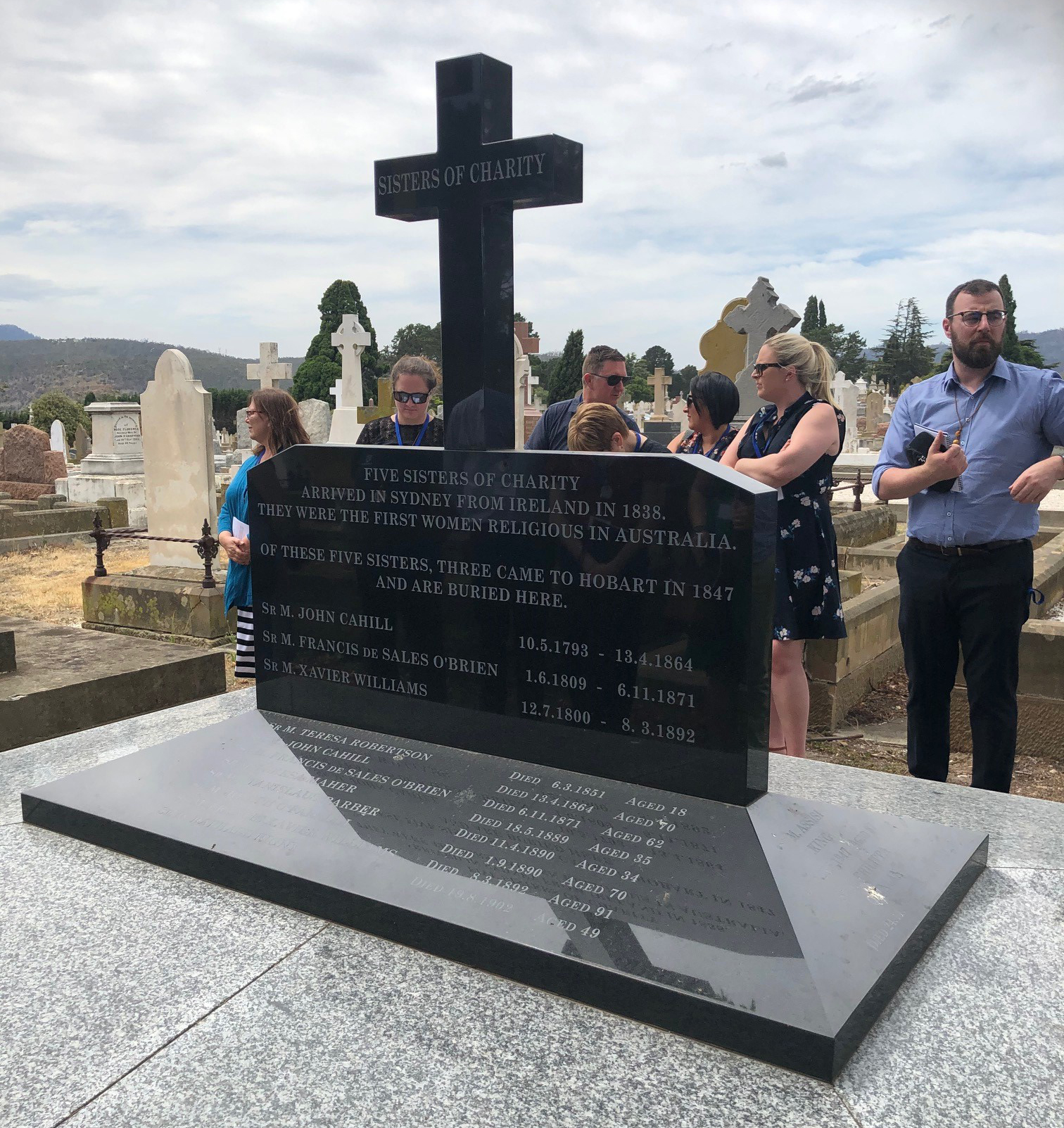 Pilgrims paying their-respects at the-final resting place of the Three Sisters at Cornelian Bay Cemetery